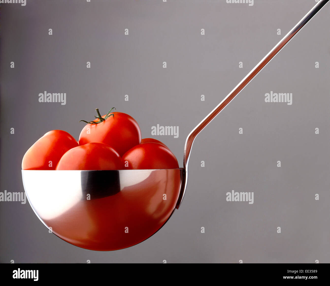 tomato soup ingredients in large ladle - Stock Image