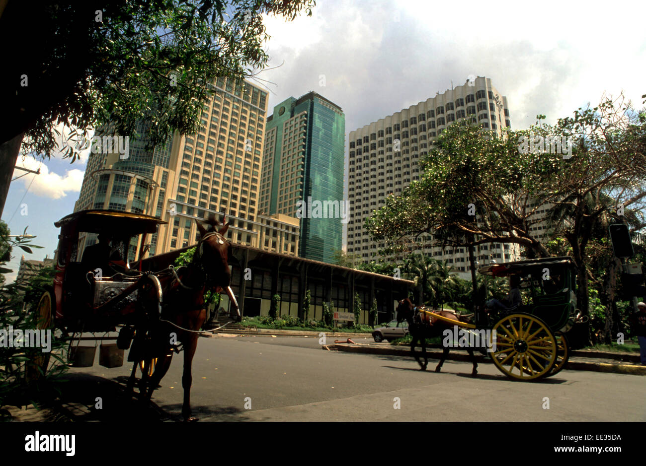 Kalesa ride, buggy horse carriage and large hotels in Malate. Manila. Philippines. Malate is an old district of - Stock Image