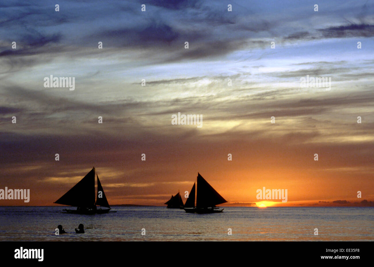 Sunset in White beach. Boracay. Boats or bankas saling near the coast. Romantic. Boracay is a small island in the - Stock Image