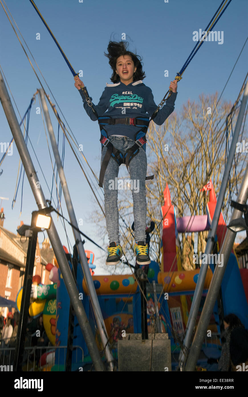 12 year old girl having fun on the bunjee trampoline at a Christmas market, High Street, Haslemere, Surrey, UK. - Stock Image