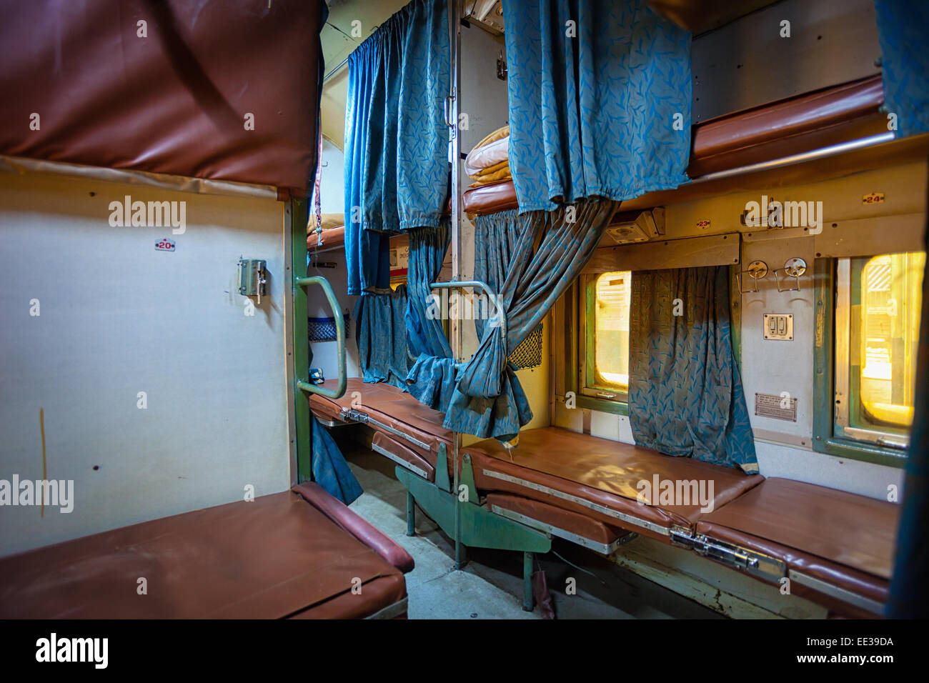 Inside a grungy and uncomfortable passenger car aboard a train in India. - Stock Image