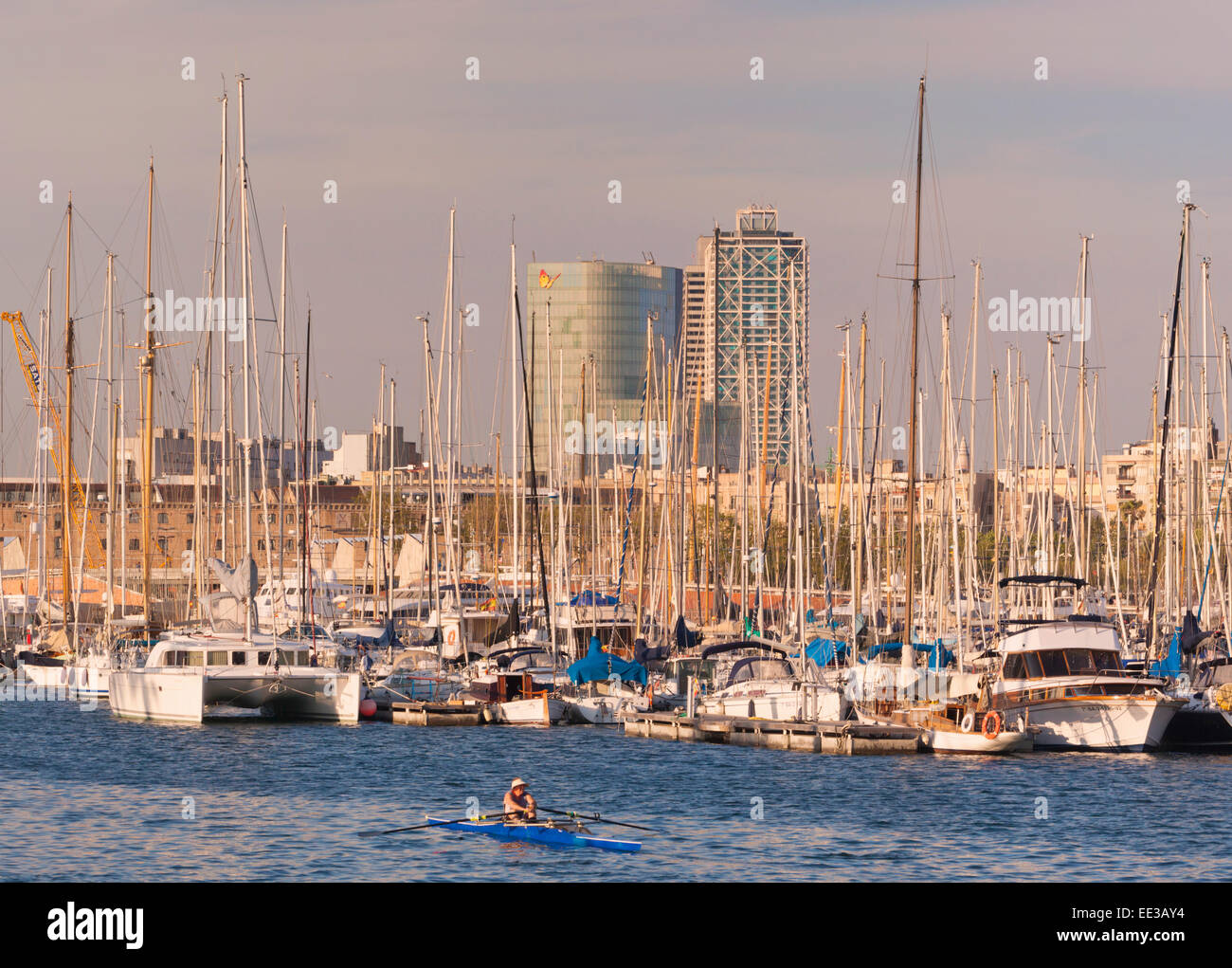 Barcelona, Spain.  Man sculling amongst luxury yachts in Port Vell. - Stock Image