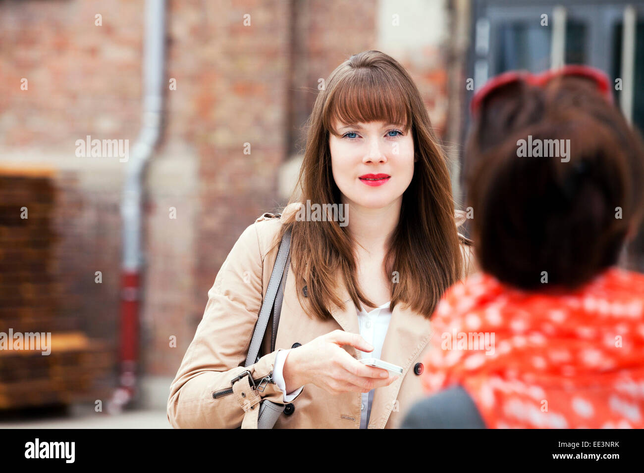 Young woman text messaging outdoors, Munich, Bavaria, Germany - Stock Image