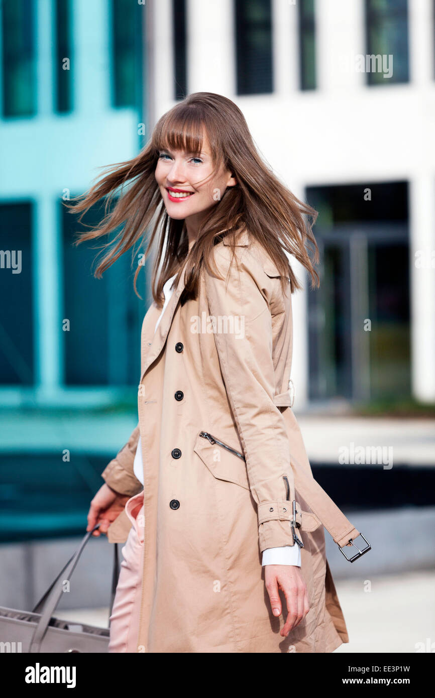 Young woman with blowing hair outdoors, Munich, Bavaria, Germany - Stock Image
