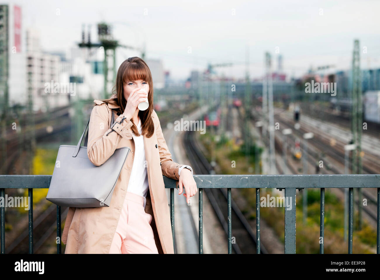 Young woman drinking coffee outdoors, Munich, Bavaria, Germany - Stock Image