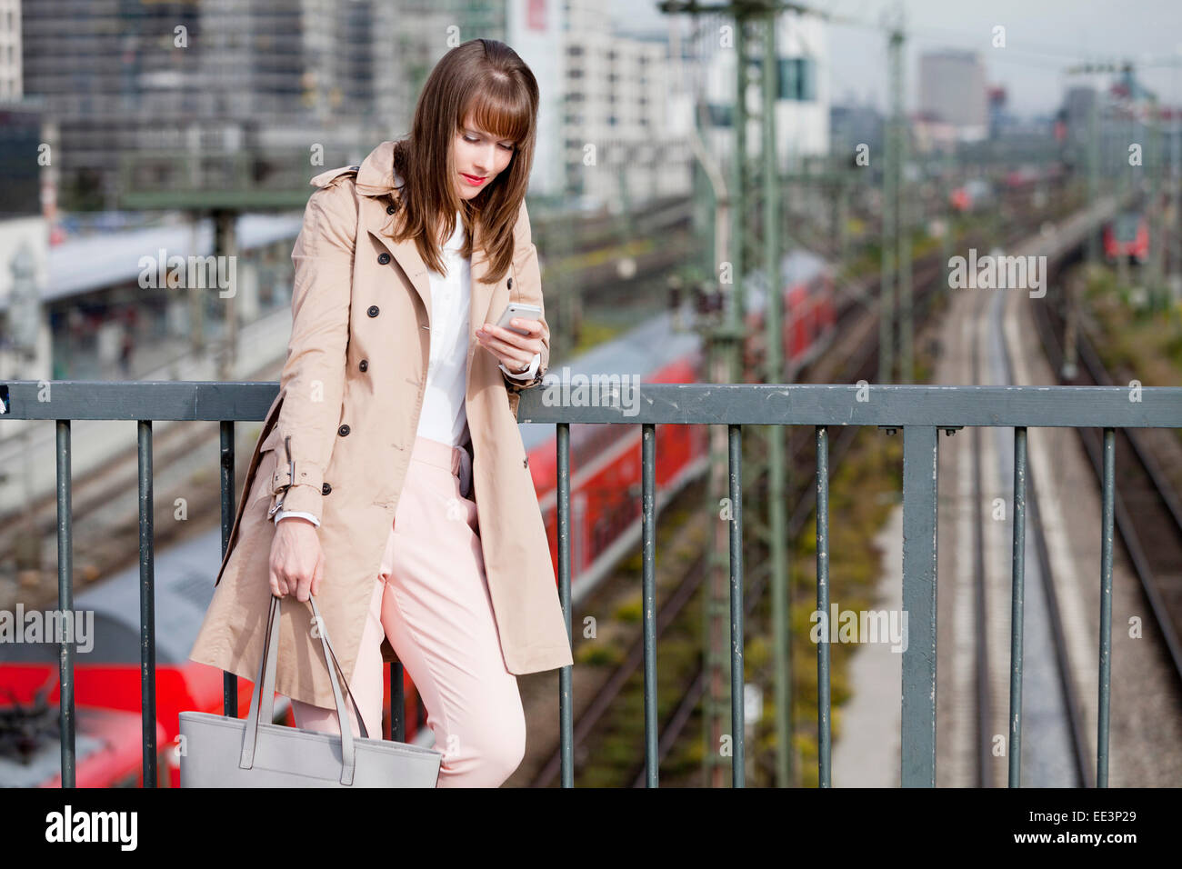 Young woman using phone outdoors, Munich, Bavaria, Germany - Stock Image