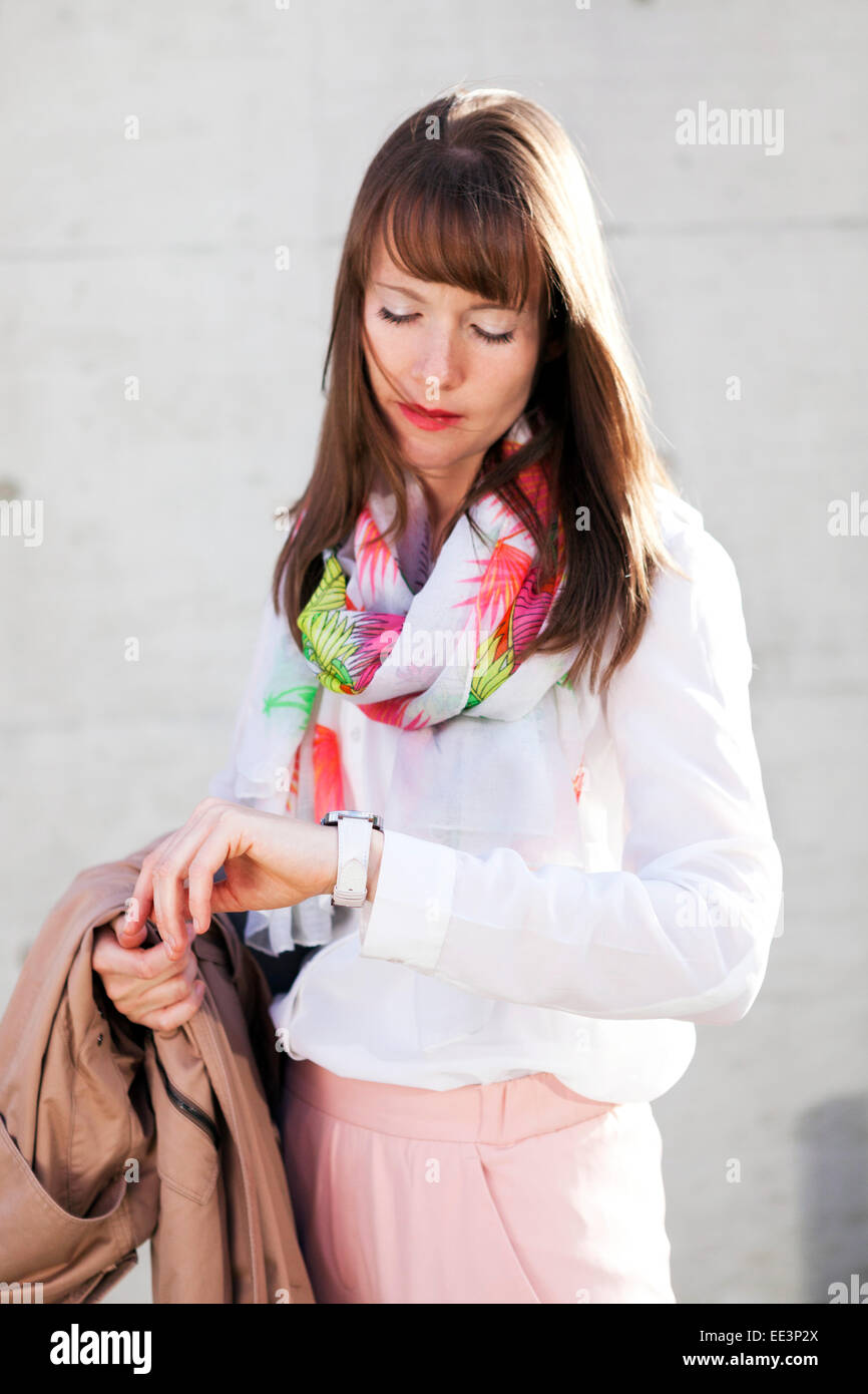 Young woman checking the time outdoors, Munich, Bavaria, Germany - Stock Image