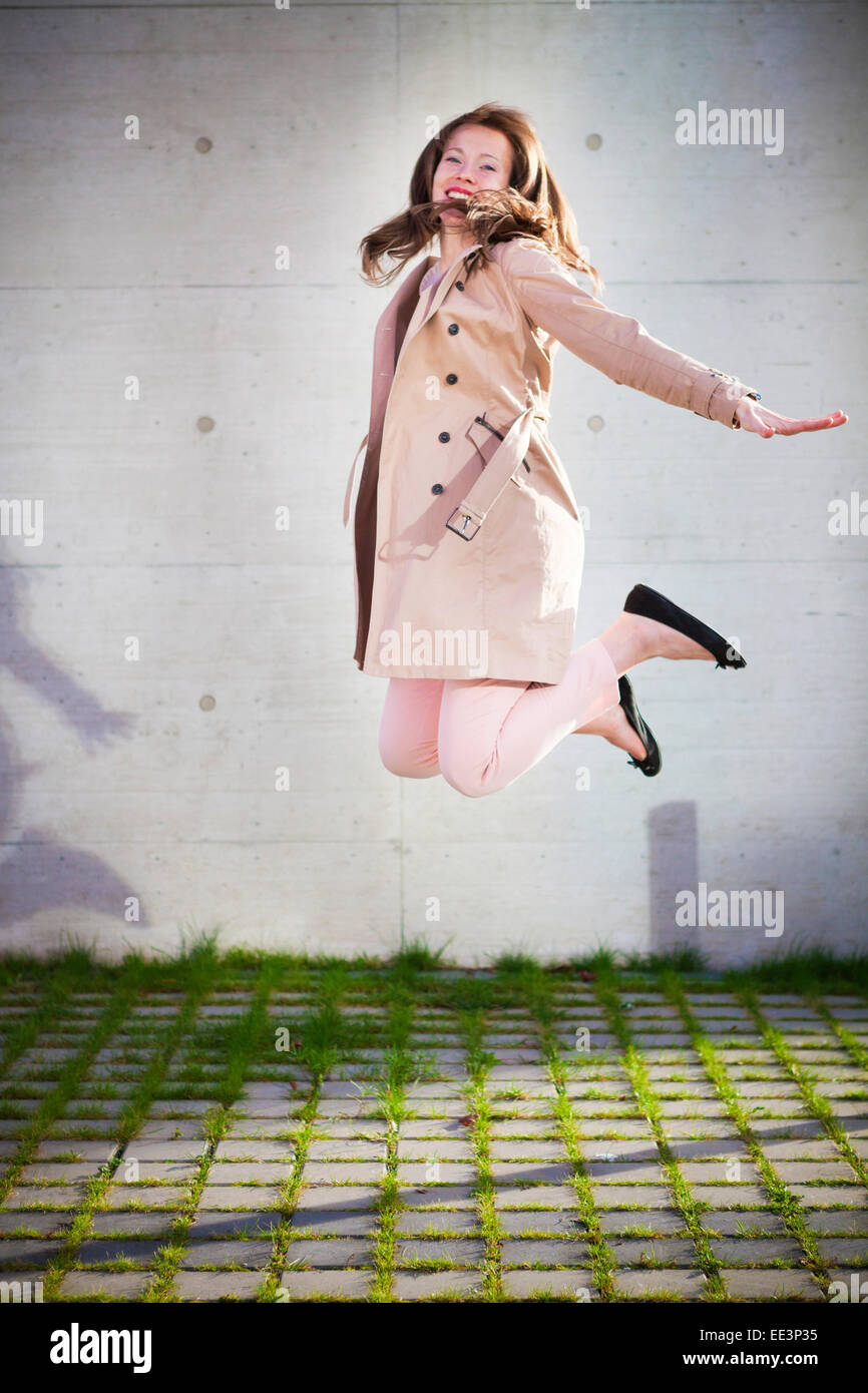 Young woman jumping outdoors, Munich, Bavaria, Germany - Stock Image