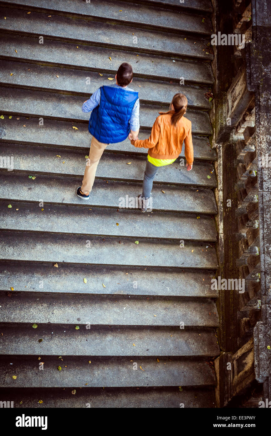 Young couple walking up steps, Munich, Bavaria, Germany - Stock Image