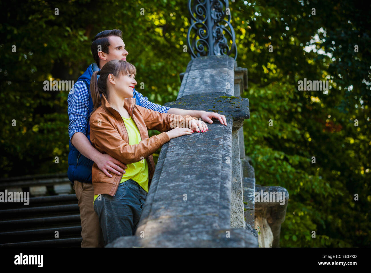 Young couple standing on staircase outdoors, Munich, Bavaria, Germany Stock Photo