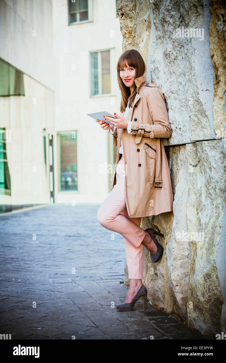 Young woman using digital tablet outdoors, Munich, Bavaria, Germany - Stock Image