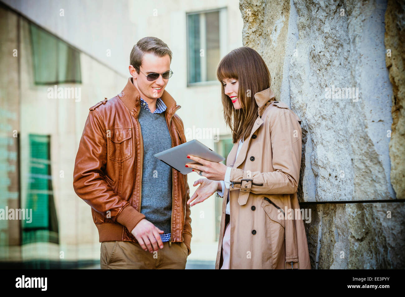 Young couple using digital tablet outdoors, Munich, Bavaria, Germany - Stock Image