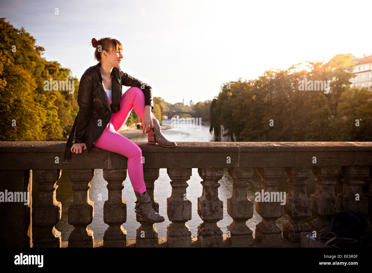 Young woman day dreaming on bridge, Munich, Bavaria, Germany - Stock Image