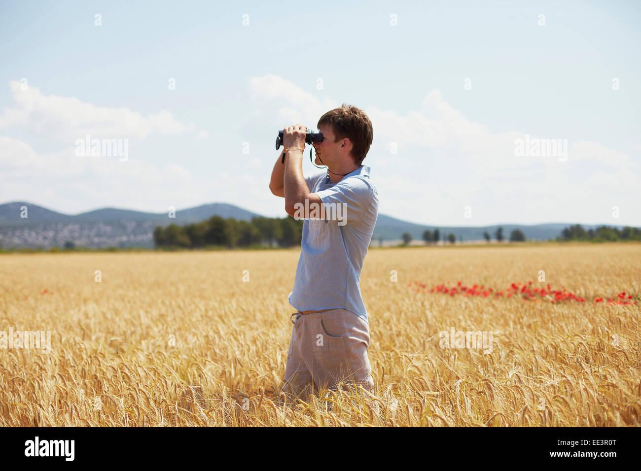 Man On Field Looking Through Binoculars, Croatia, Dalmatia, Europe Stock Photo