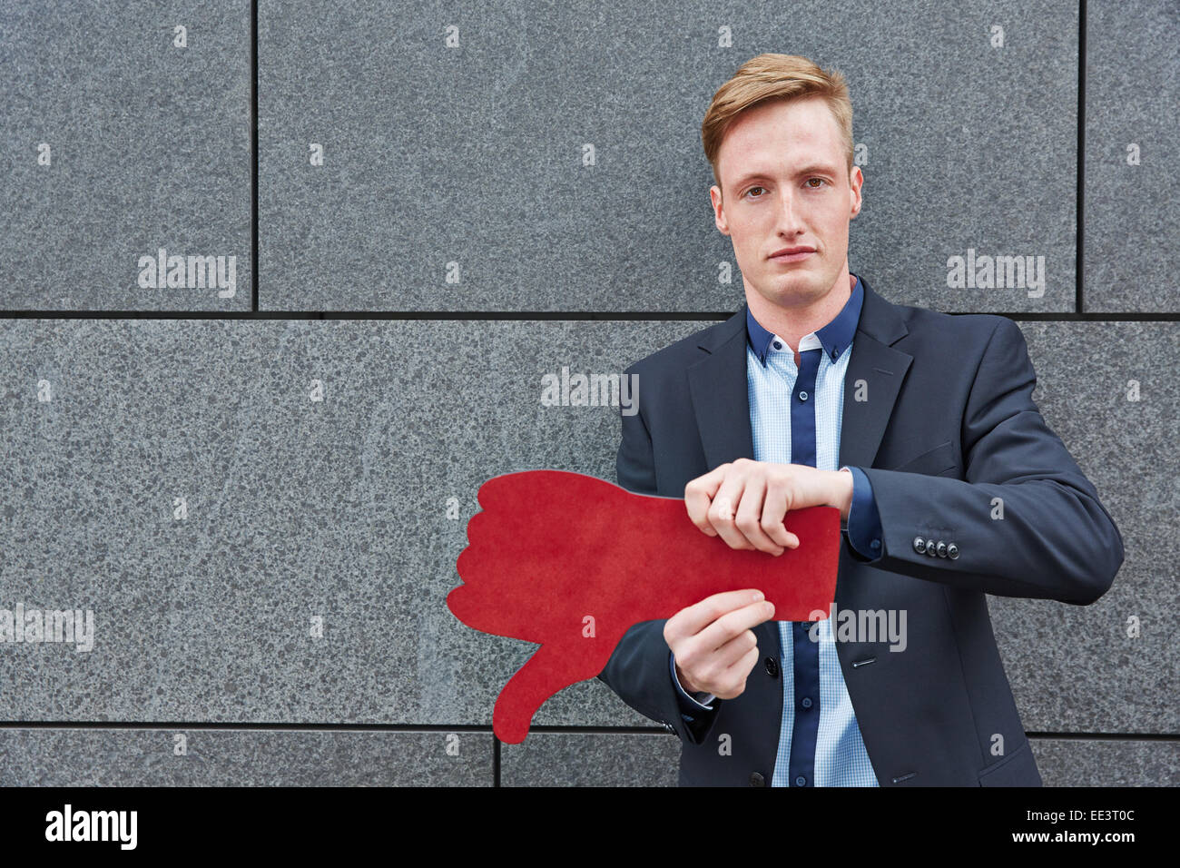 Unsatisfied business man holding red thumbs down - Stock Image