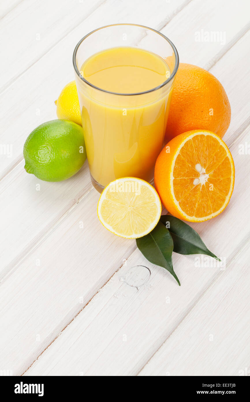 Citrus fruits and glass of juice. Oranges, limes and lemons. Over white wood table background - Stock Image