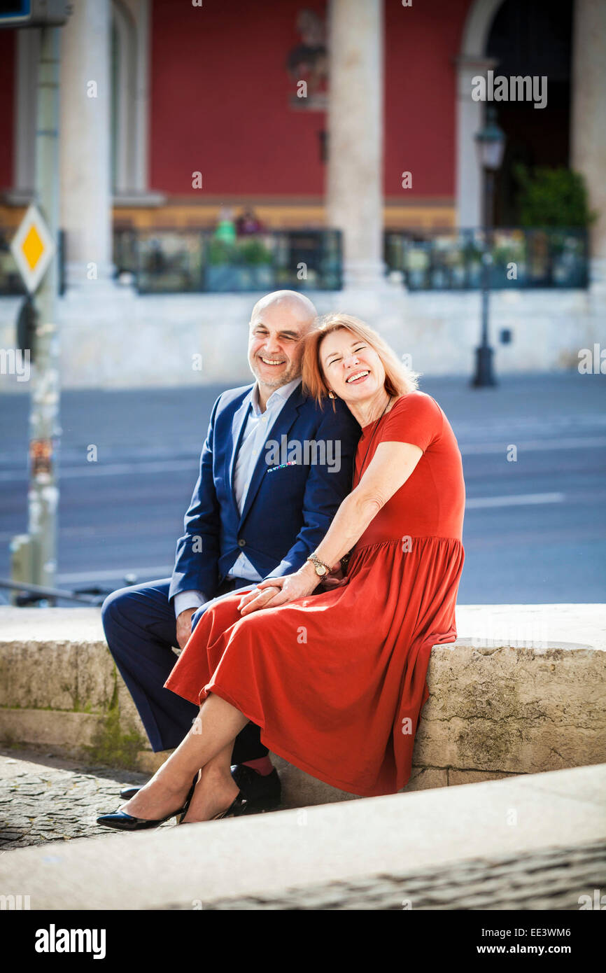 Happy senior couple sitting by street, Munich, Bavaria, Germany - Stock Image