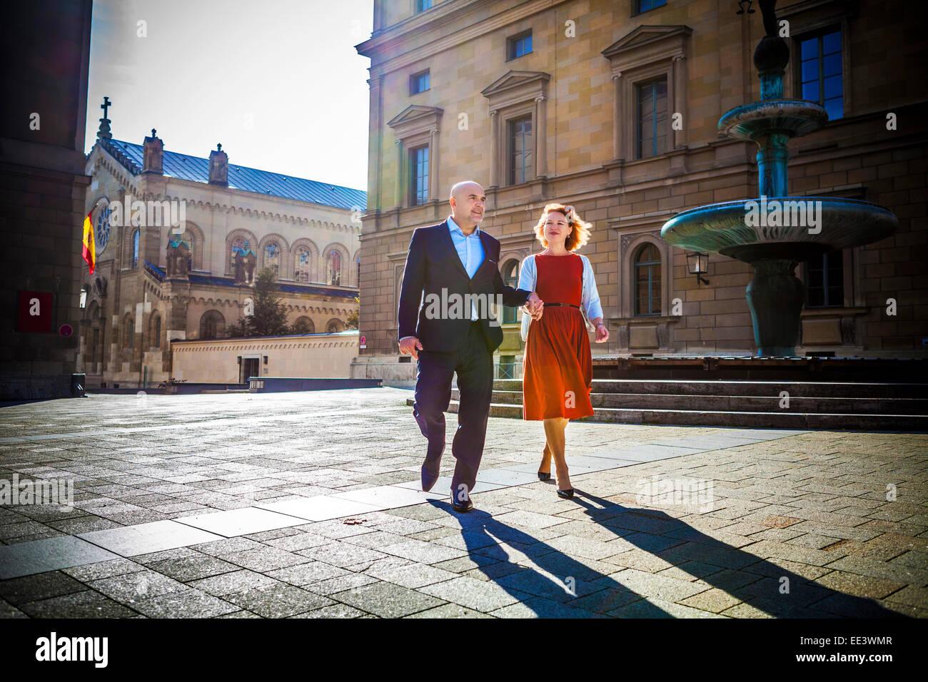 Senior couple walking in town, Munich, Bavaria, Germany Stock Photo