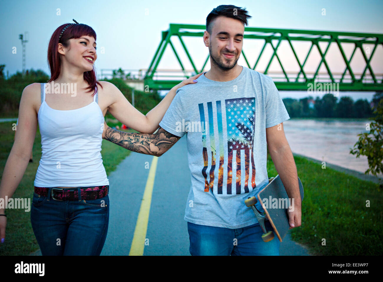 Young couple with skateboard taking a walk outdoors - Stock Image
