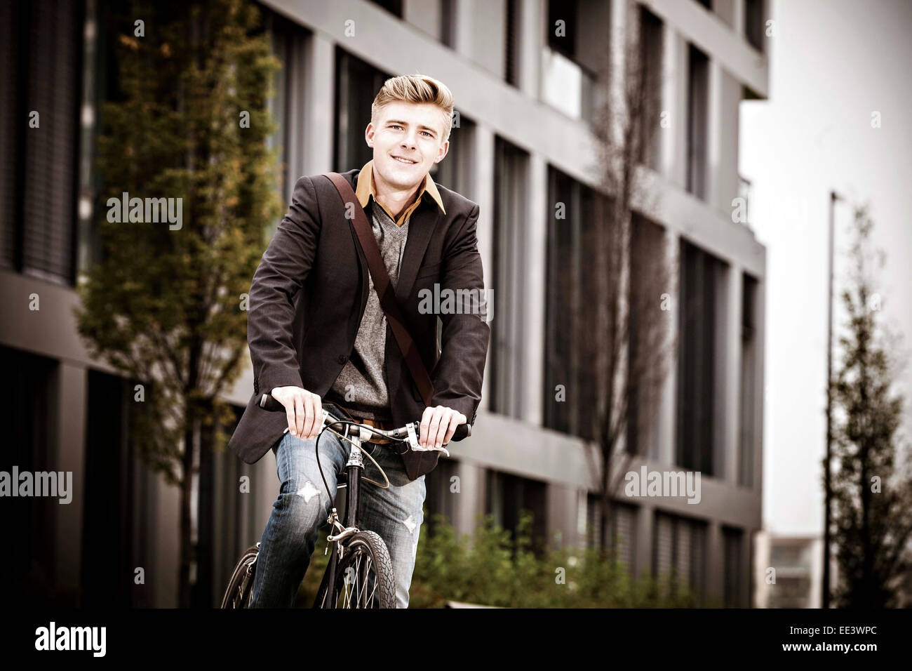 Young businessman with bicycle, Munich, Bavaria, Germany - Stock Image