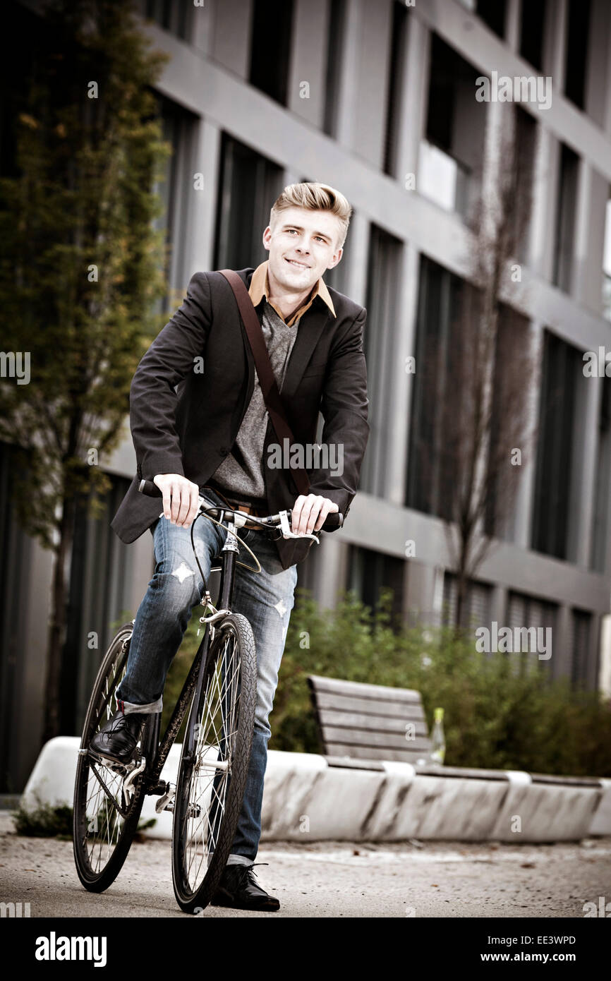 Young businessman with bicycle on city street, Munich, Bavaria, Germany - Stock Image