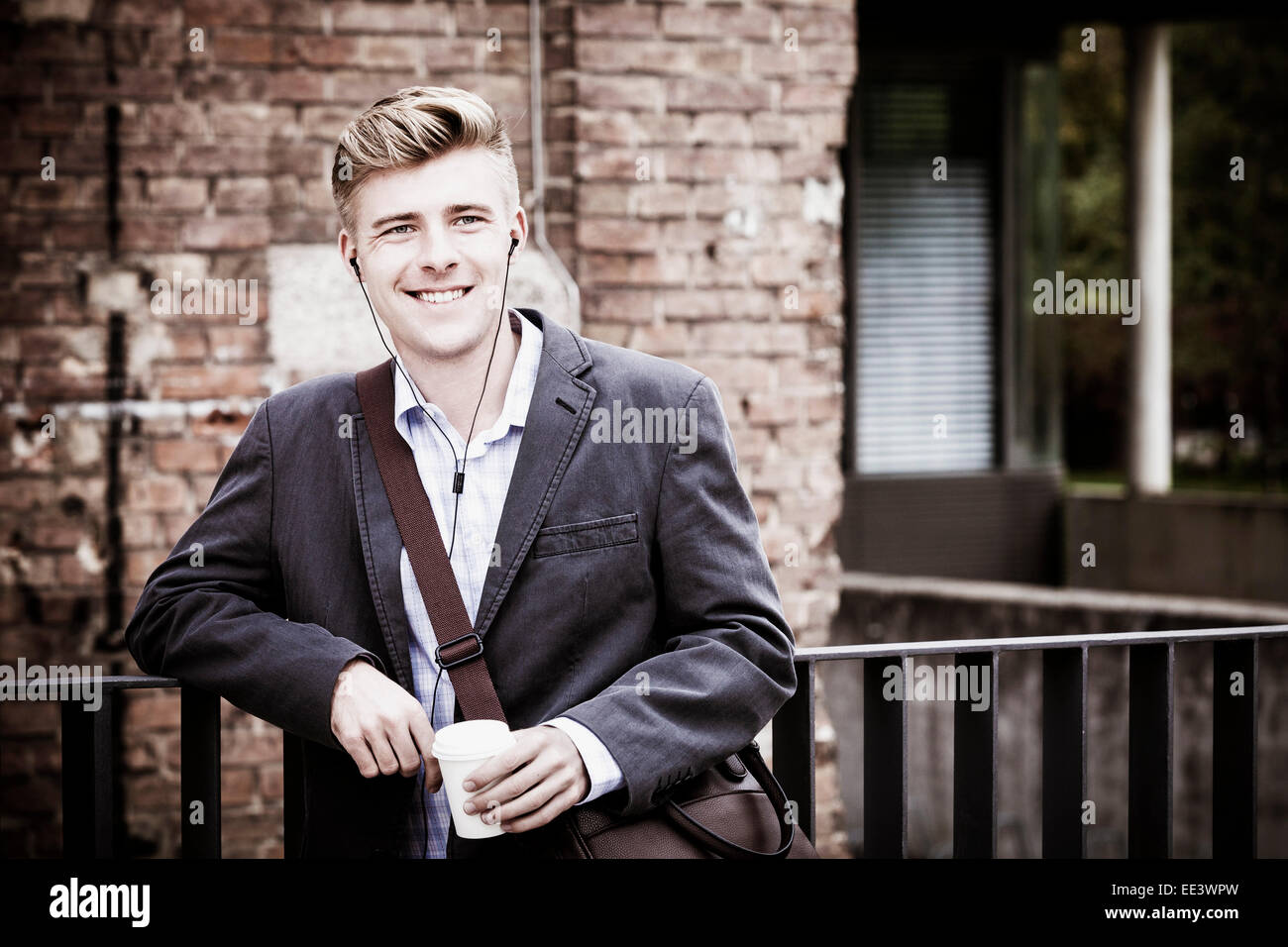 Young businessman with headphones and coffee cup, Munich, Bavaria, Germany - Stock Image