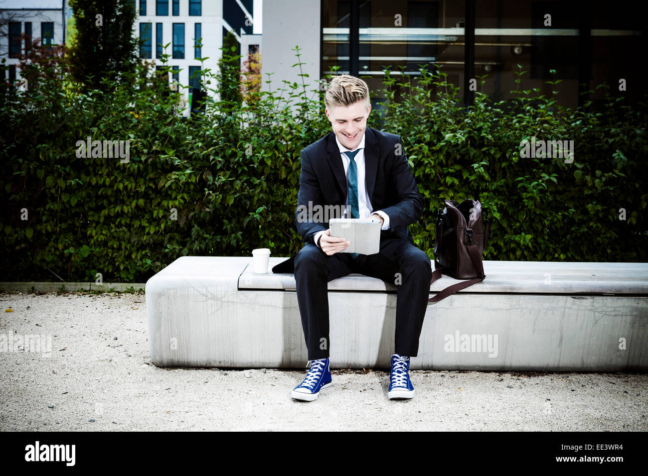 Young businessman using digital tablet outdoors, Munich, Bavaria, Germany - Stock Image