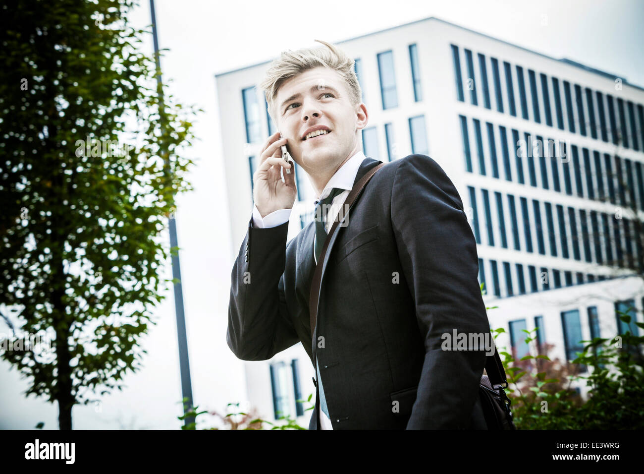 Young businessman using phone, Munich, Bavaria, Germany - Stock Image