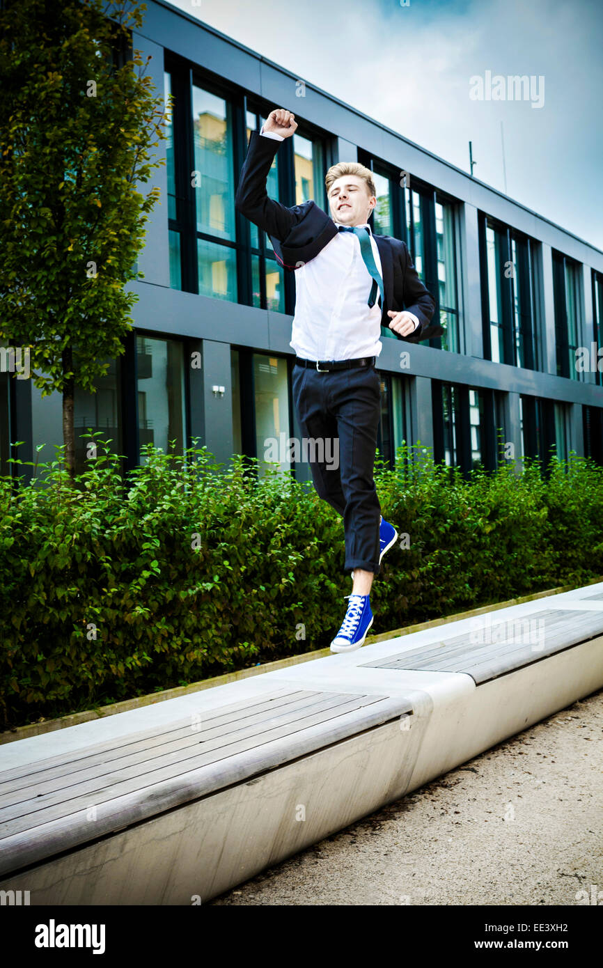 Young businessman jumps in air cheering, Munich, Bavaria, Germany Stock Photo