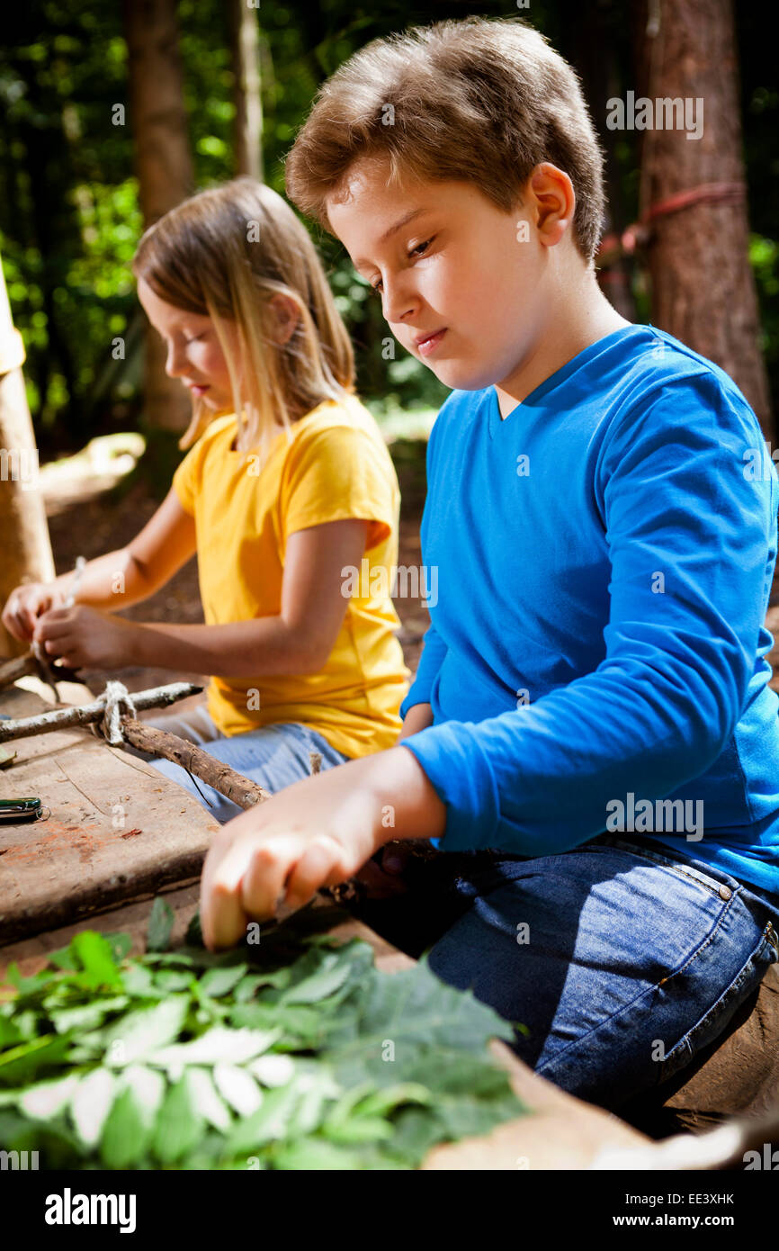 Children crafting in a forest camp, Munich, Bavaria, Germany Stock Photo