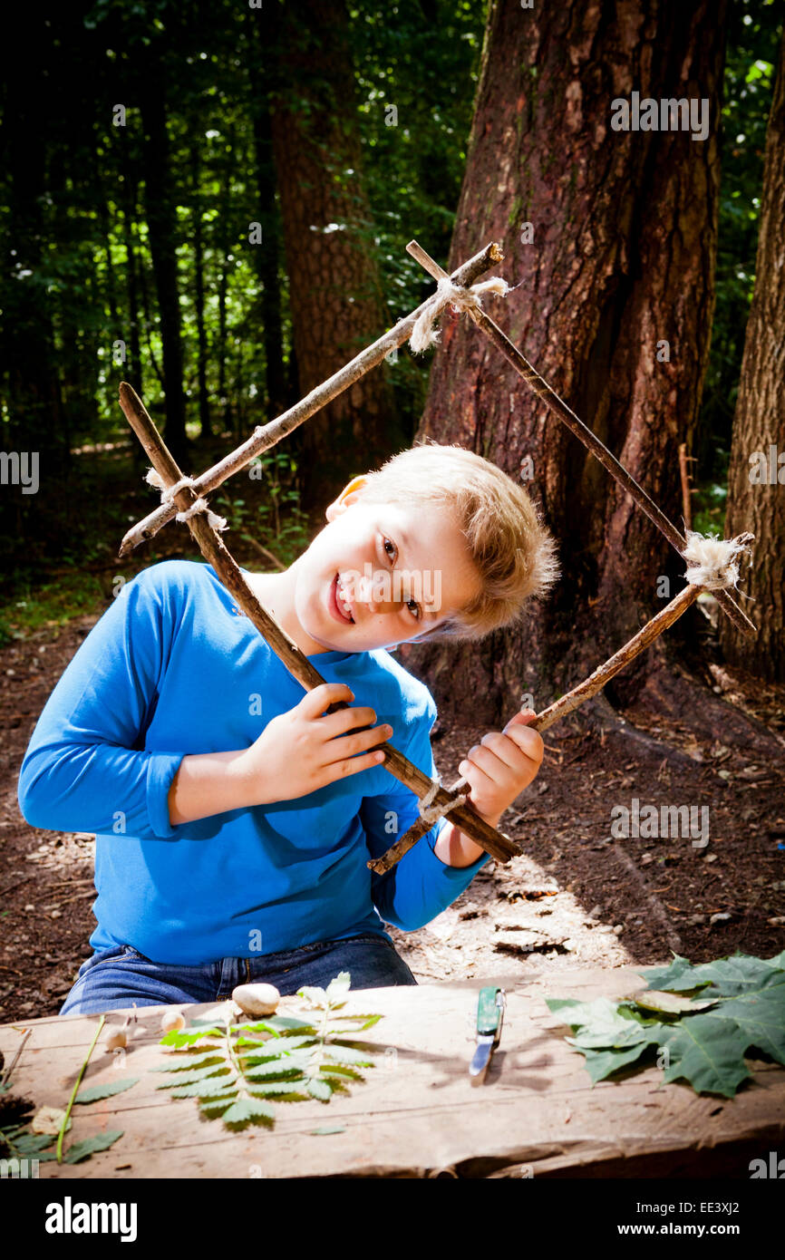 Boy crafting in a forest camp, Munich, Bavaria, Germany - Stock Image