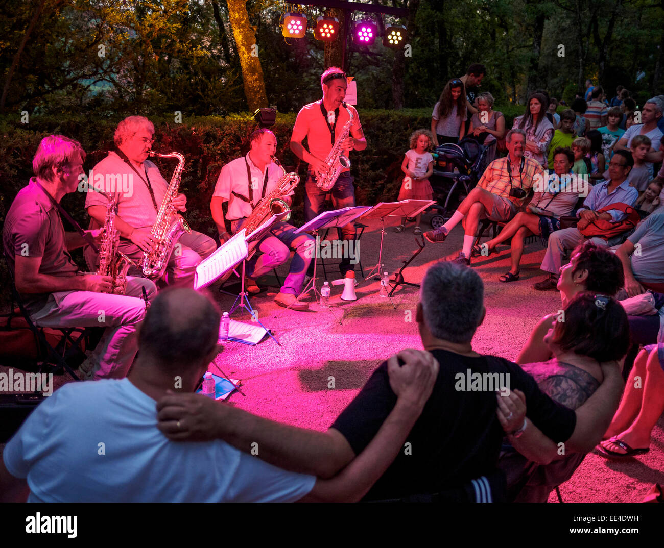 Visitors to a candlelight night at the gardens of Chateau Marqueyssac listen to the saxophone quartet Flexi-Sax - Stock Image