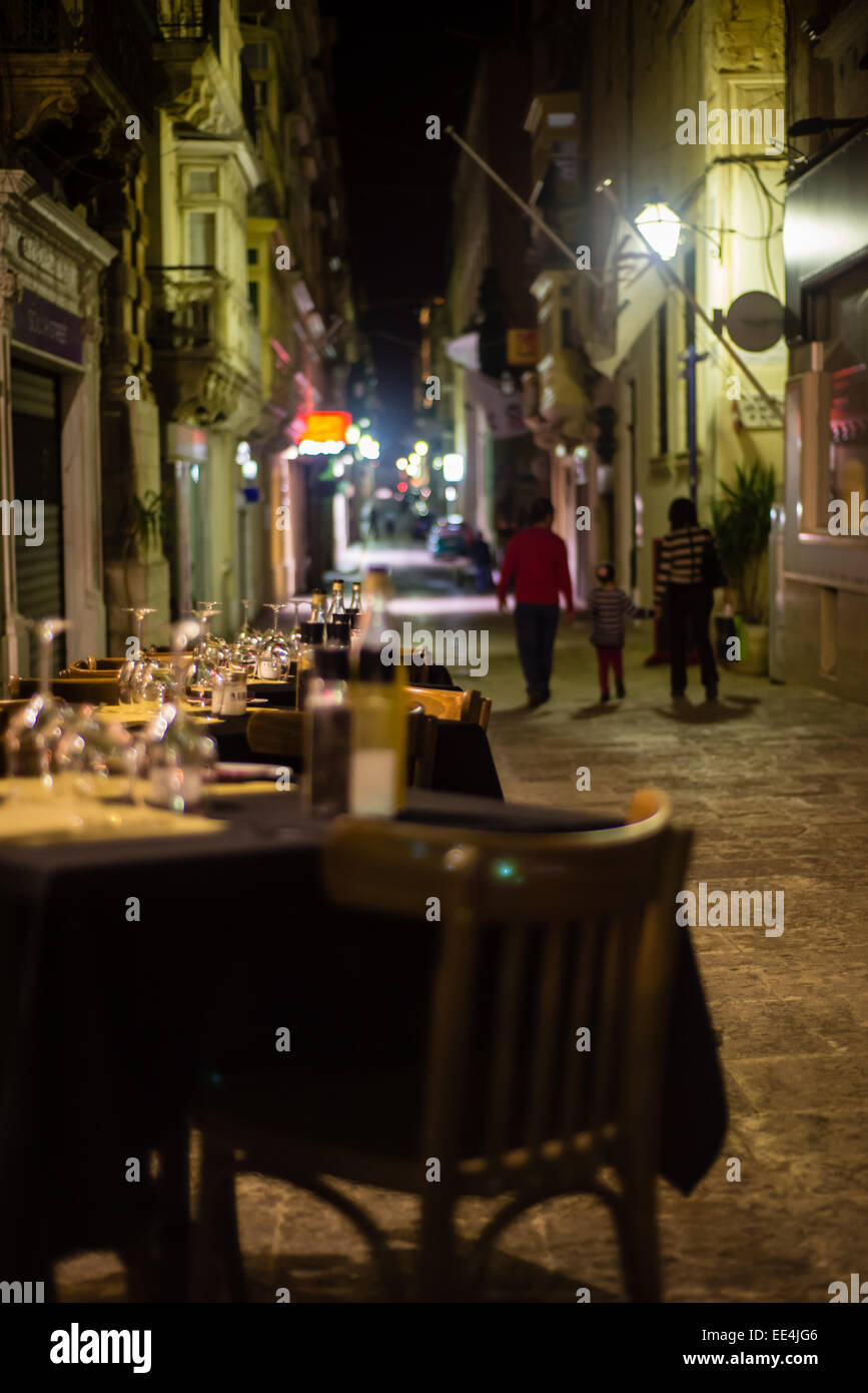 Restaurant tables in an alley in Valletta, Malta. - Stock Image