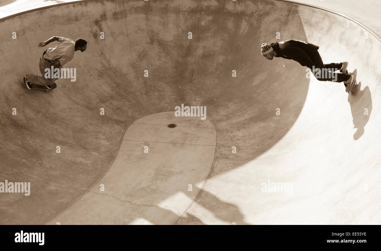 Two young mens cruising in a concrete bowl at the famous venice beach skatepark - Stock Image