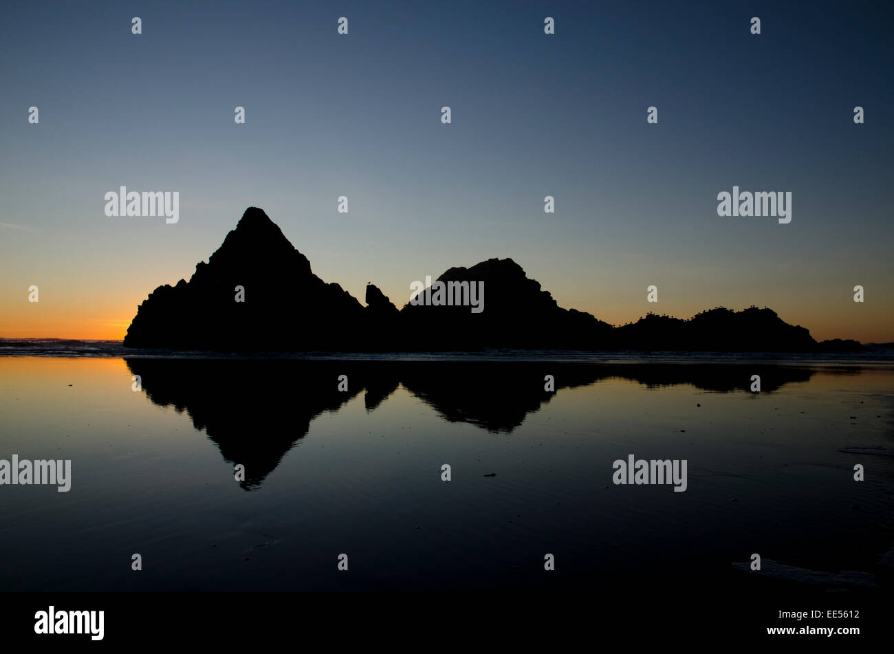 Symmetric reflexion of rocks in front of a beach during the sunset - Stock Image