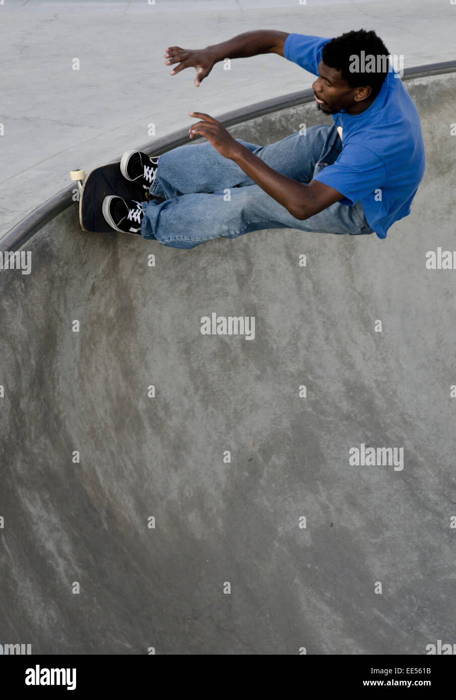 Skateboarder carving in bowl during the day - Stock Image
