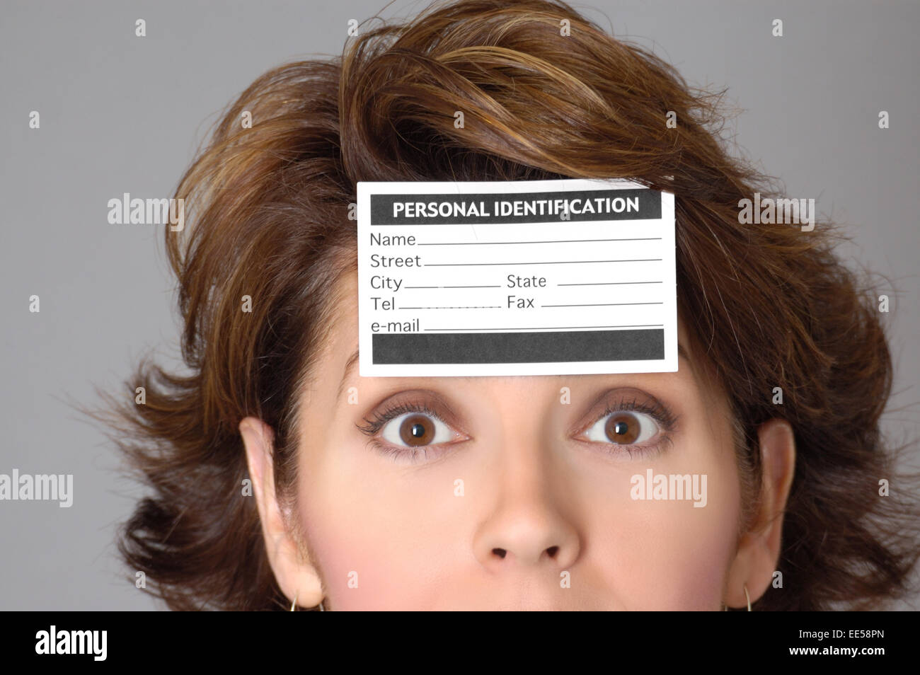 Woman wearing an identification card on her forehead.  Can represent privacy issues, identity theft, citizenship - Stock Image