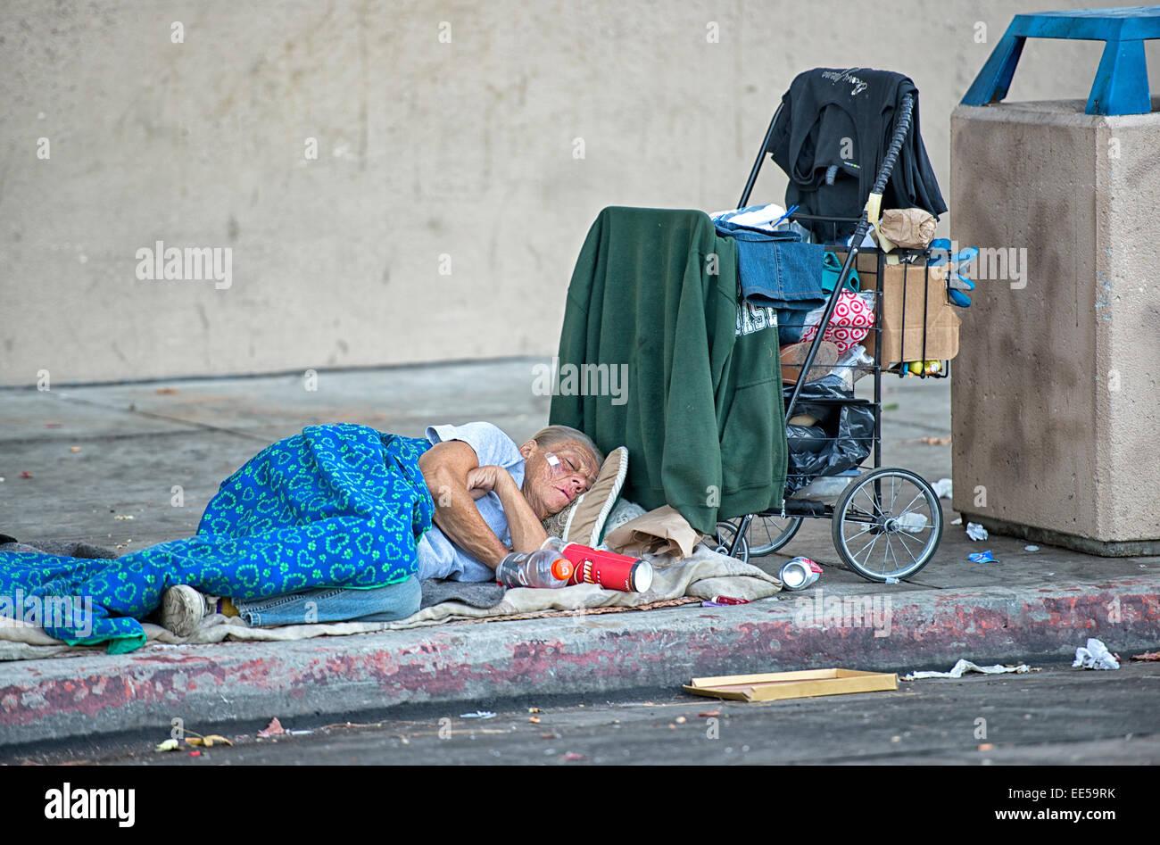 Homeless Elderly Woman Sleeping On Sidewalk Next To
