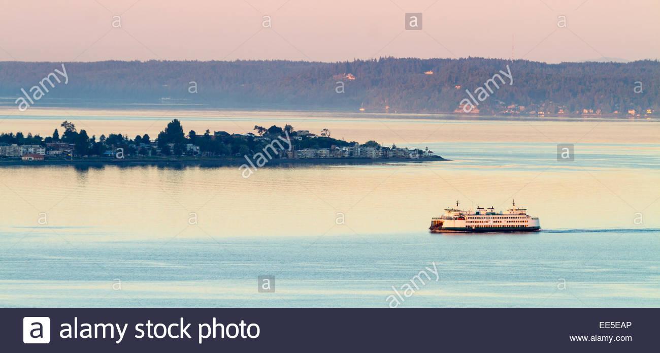 Washington State Ferry passing Alki Point during sunrise at Elliot Bay - Seattle - Washington - USA - Stock Image