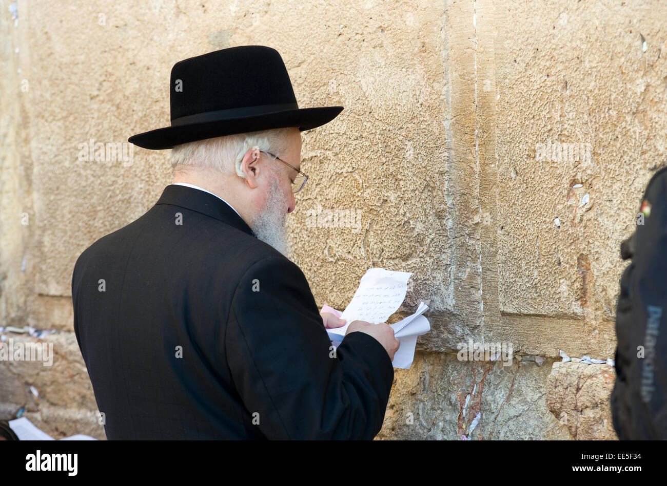 A jewish man is reading from a paper in front of the western wall in the old city of Jerusalem - Stock Image