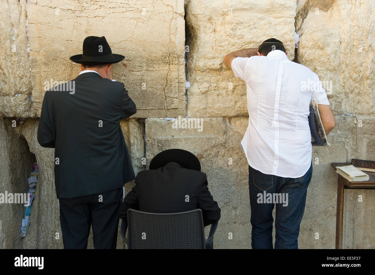 JERUSALEM, ISRAEL - OCT 06, 2014: Three jewish man are praying against the western wall in the old city of Jerusalem - Stock Image