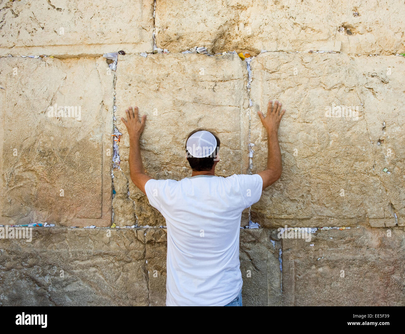 A jewish man is praying against the western wall in the old city of Jerusalem - Stock Image