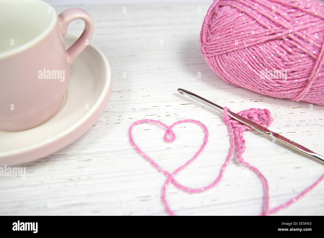 pink crochet background with yarn heart and coffee cup and crochet hook on wooden background - Stock Image