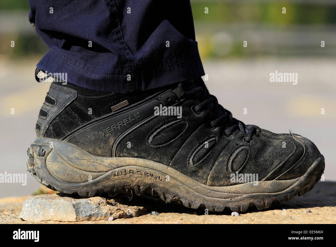 Keeping fit - healthy lifestyle - muddy black walking boot close up - Stock Image