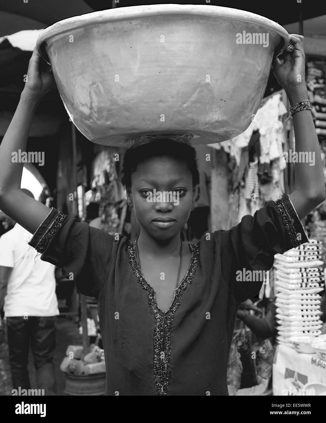 Girl carrying food in Ghana Market. These girls helps shoppers carry their food in markets and make a small living - Stock Image