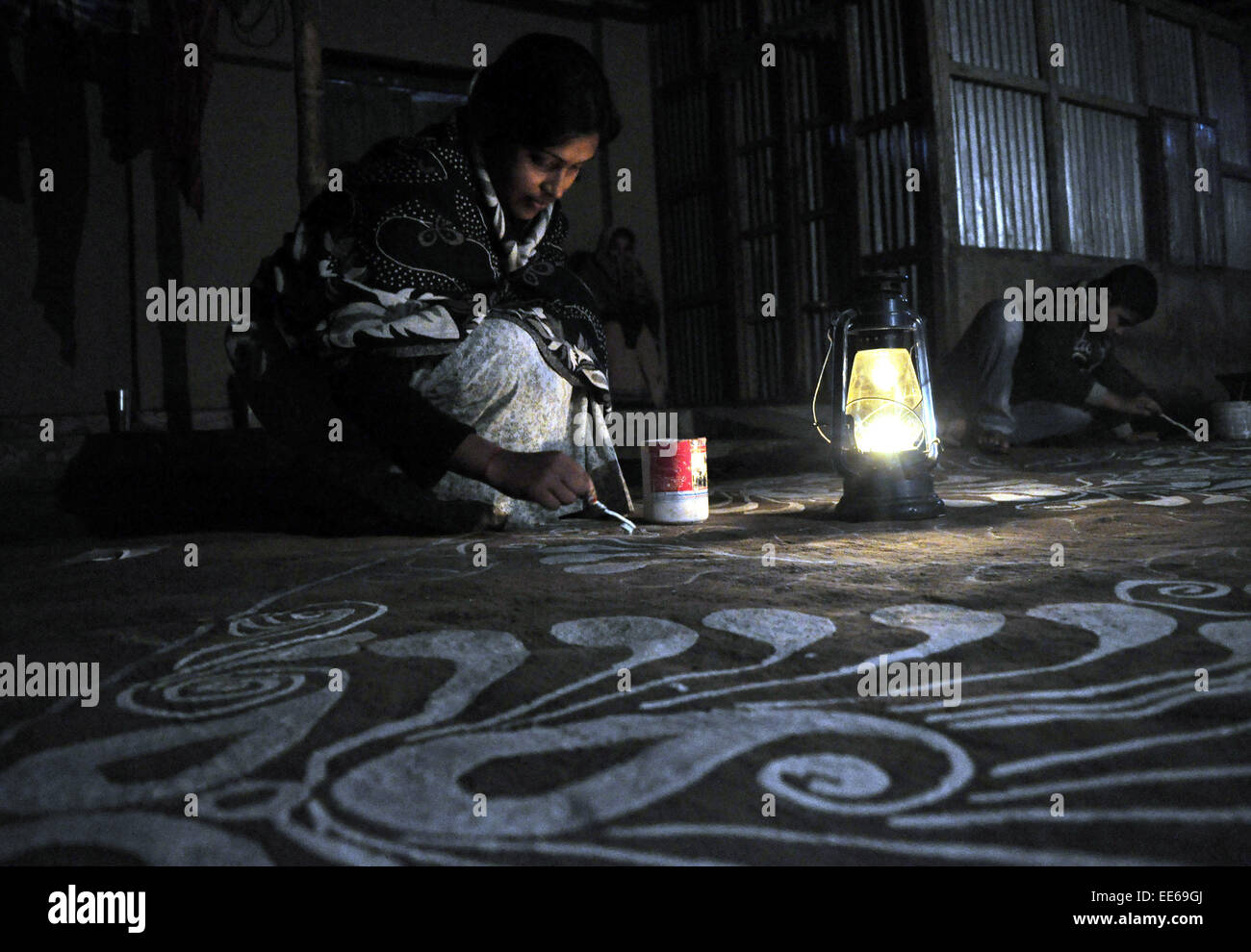 "(150114) -- AGARTALA, Jan. 14, 2015 (Xinhua) -- A woman paints ""alpona"" on the floor at Lankamura, 10 km away from Stock Photo"