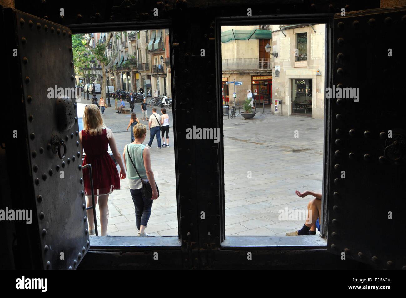 A beggar sits in the door way of a church,  Barcelona. Basílica de la Mercé Spain - Stock Image