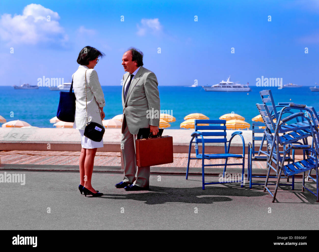 Cannes, Cote d'Azur, France. Businessman talking to younger woman by the seafront. Yachts behind - Stock Image