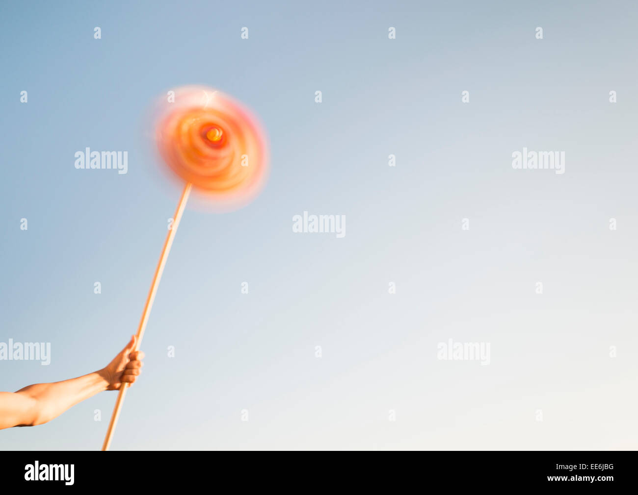 Hand holding pinwheel toy spinning in the wind. Conceptual image of freedom, carefree lifestyle and having fun. - Stock Image