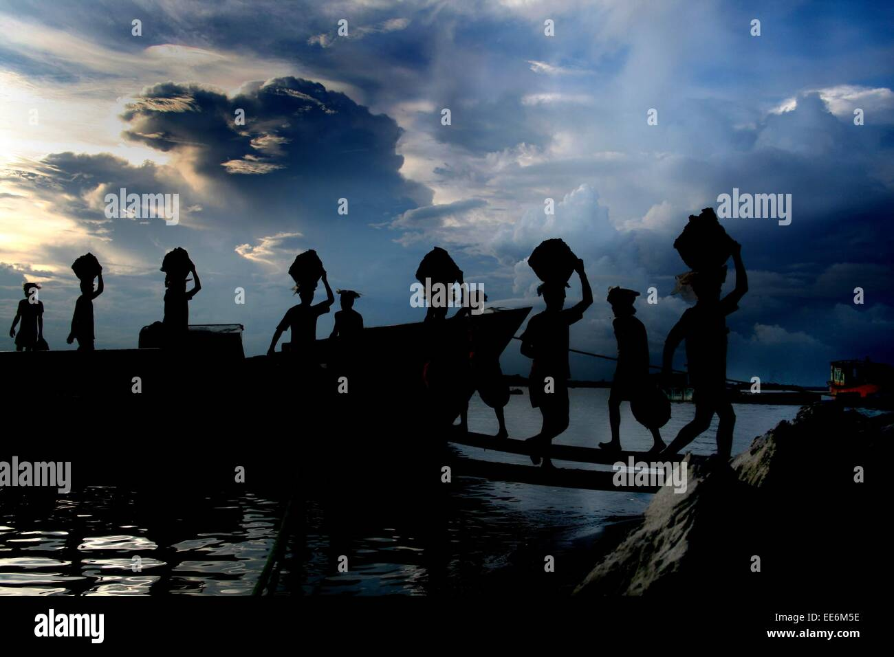 Bangladesh 10 January 2015. Workers unload earthen pots from a boat at a nearby village of the Bangladeshi capital - Stock Image